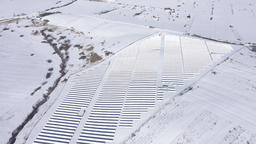 Aerial drone view of snow covered solar panel park, photovoltaic power station Footage