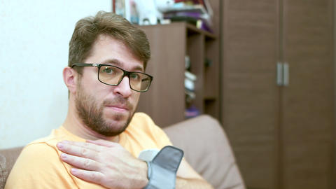 A bearded man with glasses measures his blood pressure. He is upset Live Action