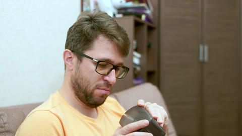 A bearded man with glasses measures his blood pressure. Turns on the device Live Action