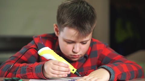 A boy teenager in a plaid shirt draws a 3D plastic figure with a pen Footage