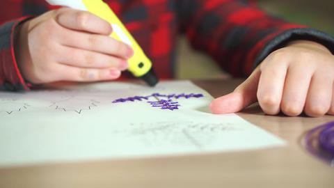 Close-up boy teenager in a plaid shirt draws a 3D plastic figure with a pen Footage