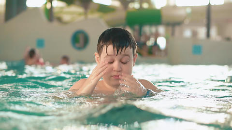 Boy teenager in the water in a public indoor swimming pool water park Footage
