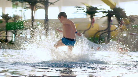 Boy teenager in the water in a public indoor swimming pool aqua park Archivo