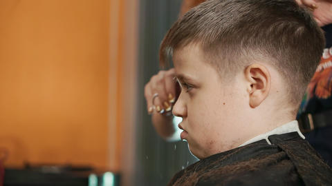 Hairdresser woman makes fashionable hairstyle boy teenager Footage