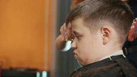 [alt video] Hairdresser woman makes fashionable hairstyle boy teenager