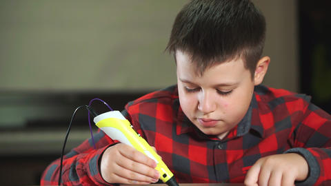 A boy teenager in a plaid shirt draws a 3D plastic figure with a pen Live Action