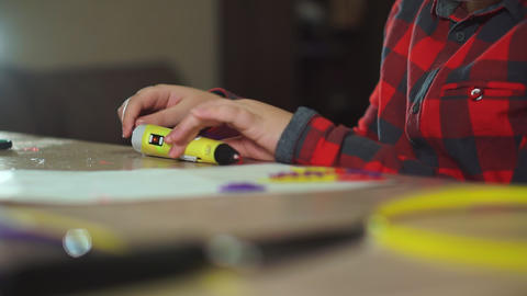 Teen boy inserts a piece of violet ABS plastic in a 3D pen. He creates a plastic Footage