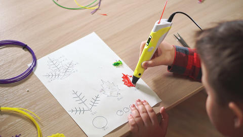 Teen boy uses a 3D pen. He creates a plant leaf from red ABS plastic Footage