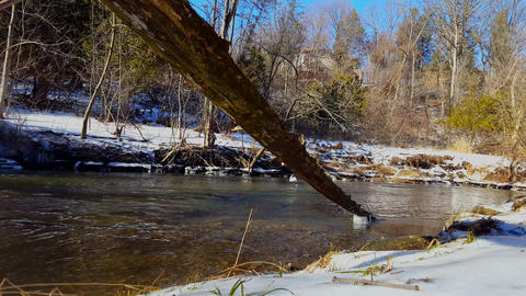 River in Winter With Snowy Bank. Residential Suburb House in the Background Footage