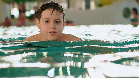 Boy teenager in the water in a public indoor swimming pool aqua park Live Action