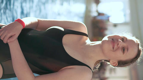 Vertical video for mobile devices. A young girl in a black bathing suit stands Footage