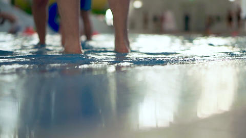 Swimming pool in public aqua park, waves close-up. Unfocused background, people Live Action