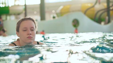Teenager girl in water in public indoor aqua park pool Footage