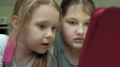 girls sisters playing on the tablet in the room, web surfing, rest Footage