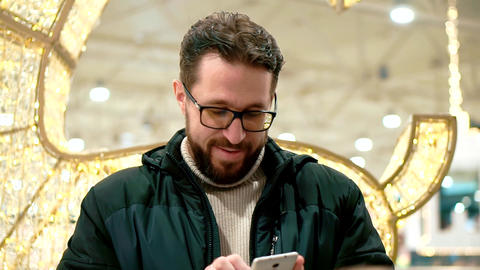 Bearded man with glasses, looks into the smartphone and reads the message Live Action