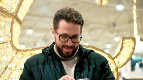 Bearded man with glasses, looks into the smartphone and... Stock Video Footage