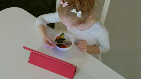 little girl eats and plays using computer tablet. web surfing Footage