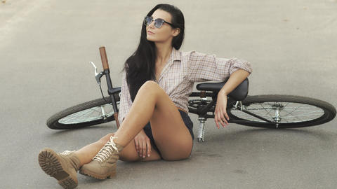 Young woman sitting with a bicycle outdoor ビデオ