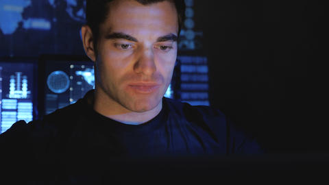 Handsome male hacker programmer works at a computer at night in a data center Footage