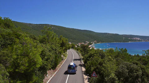 Aerial - Car with a roof box drives by the road at seaside vacation spot Footage