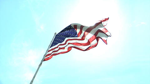 An American flag slowly flies against the sky Footage
