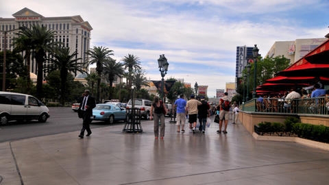 Static time-lapse shot of tourists walking along the sidewalk in Las Vegas Footage