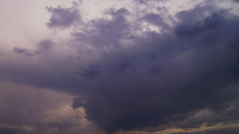 Thunderclouds roll across the sky with a weak sun shining through Footage