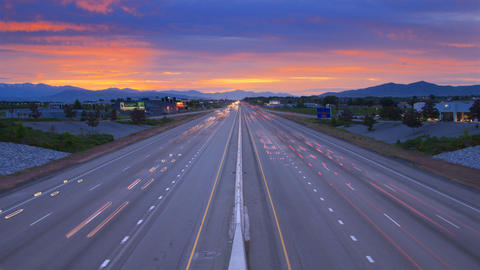 Time-lapse shot of traffic on a highway in Utah taken from an overpass at sunset Footage