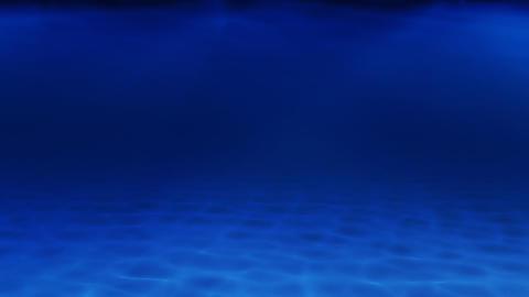 Sunbeams pierce a deep blue sea, illuminating a sandy seabed Footage