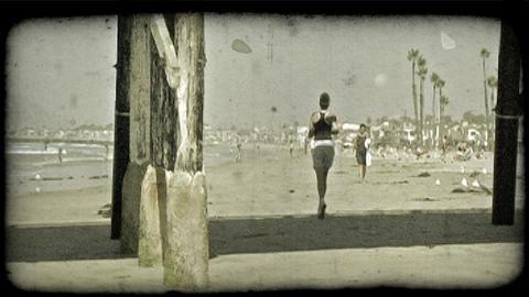 Woman jogs along beach. Vintage stylized video clip Footage