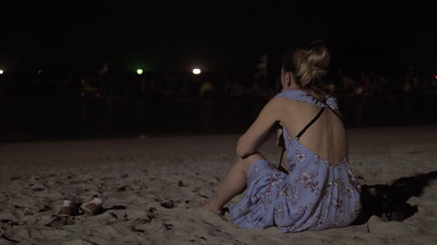 Young woman enjoying sea during sunset. Sitting on the sand beach. Looking at GIF