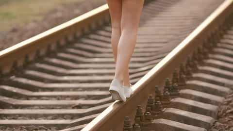 Woman balancing on train rail. Beauty, freedom, summer travel concept Footage