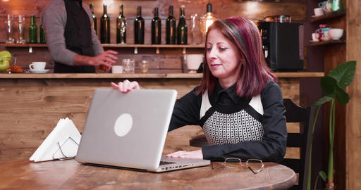 Businesswoman in her 40s opens a laptop and starts working on it ビデオ