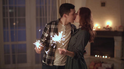 Happy young couple stand with bengal lights in hands and kissing lips. Tender Footage