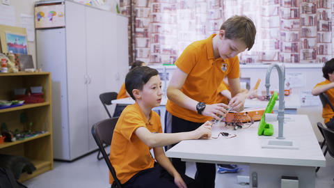 smart schoolboys work on mechanism assembling at lesson GIF