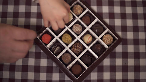 The box of candies stands on the table. Four hands taking... Stock Video Footage