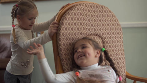 Little girl shaking his sister in a rocking chair close up. Two cute girls with Footage