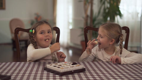 Two cute small sisters tastes chocolate tasty sugar-free candy ball after dinner Footage