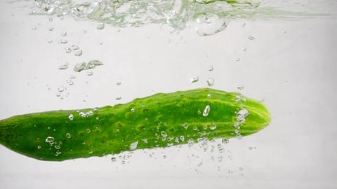 Green fresh cucumder falls into water on a white background Footage