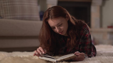 Pretty young woman in checkered shirt lying on fluffy carpet reading the book ビデオ
