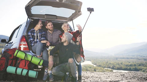 Four of young people doing selfie on smartphone, sitting leaning on trunk of suv Live Action