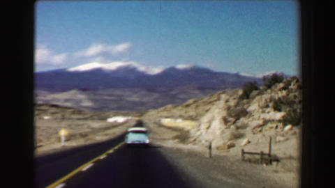 1968: Open road trip travels following 50's classic car snow capped mountains we Footage