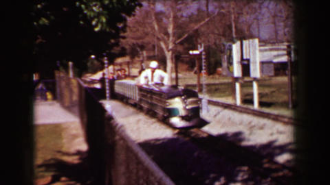 1957: Mini locomotive railroad train takes young girl and mom around park Footage