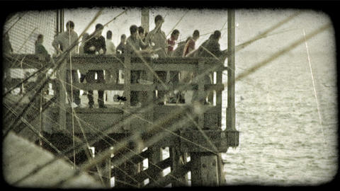 People fish off pier. Vintage stylized video clip Footage