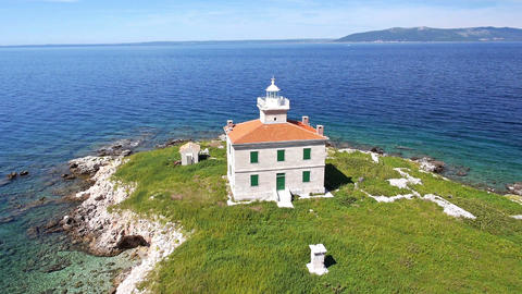 Aerial - Solitude lighthouse on a small island with green field Footage