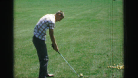 1968: Teenage boy swinging golf club behind front view with high speed slow moti Footage