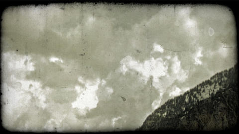 Clouds drift by mountainside. Vintage stylized video clip Footage