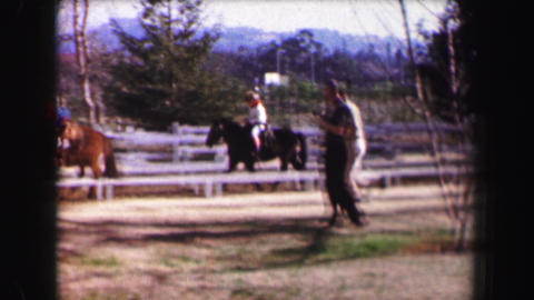 1967: Family riding horses white picket fence stables trotting course Footage