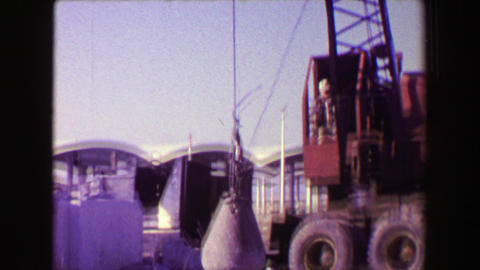 1968: Wrecking ball crane breaking packing rock backfill dirt solid Footage