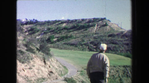 1968: Golfing man hits drive on fancy golf course into challenging fairway Footage